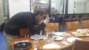 Hayden taking photos of the place settings