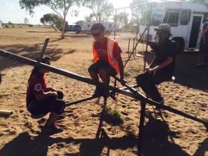 "Sara, Chris, and Logan playing on the Kulgera playground seesaw... Logan to Sara: ""Would you like to seesaw?"""