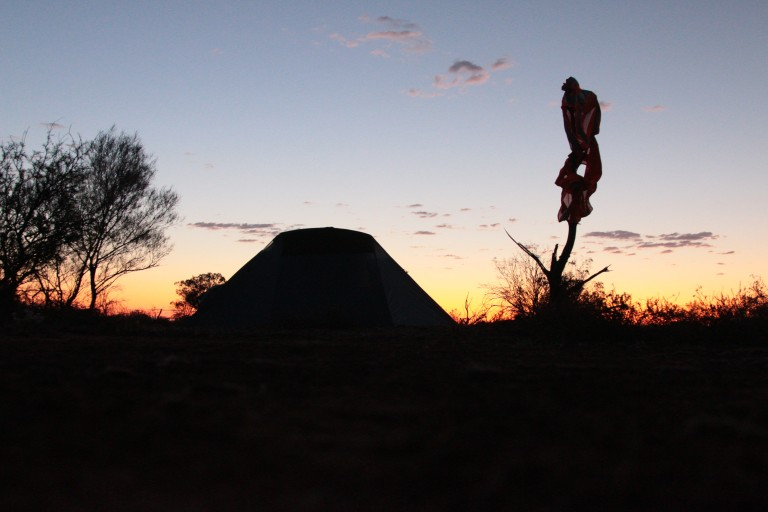 our tent and a safety vest haning on a branch watching the sunset